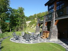 Relaxing area on the lower ground level, recently landscaped, with wood fireplace and SPA at Le Versant du Massif.